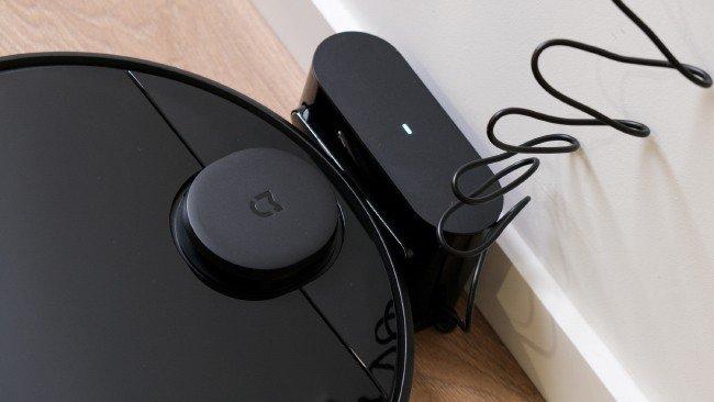 aspirador robot na base de carga em preto e chão de madeira
